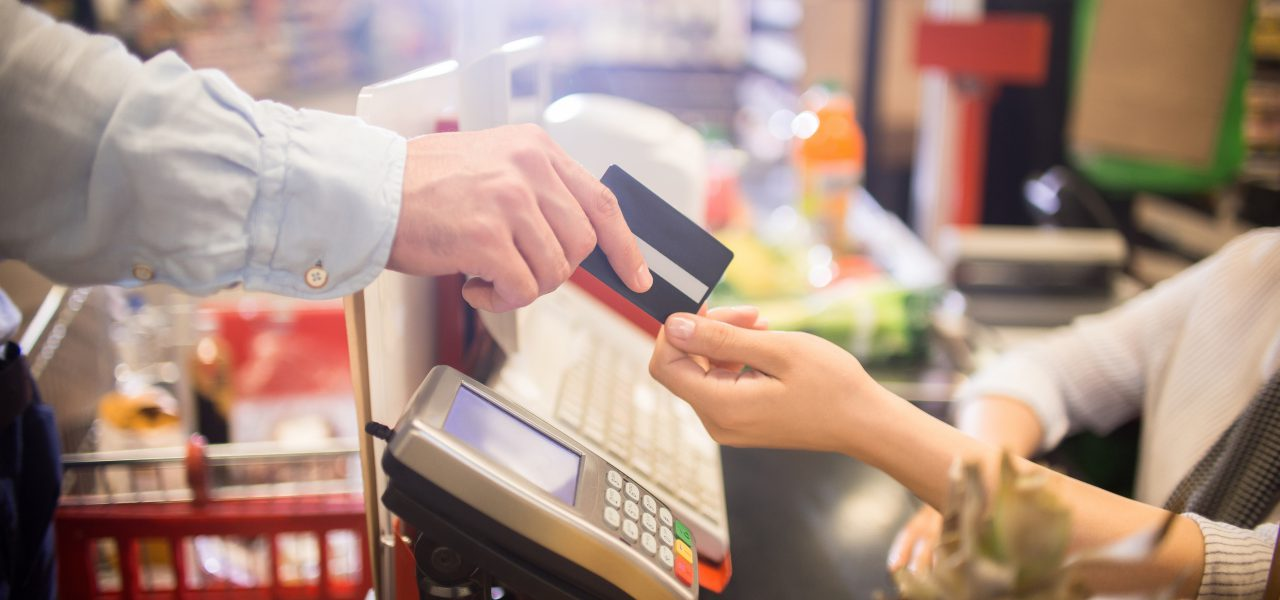 Side view close up of unrecognizable customer handing credit card to cashier paying via bank terminal at grocery store
