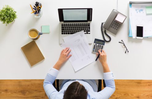 business, accounting, people and technology concept - businesswoman with laptop computer, calculator and papers working at office
