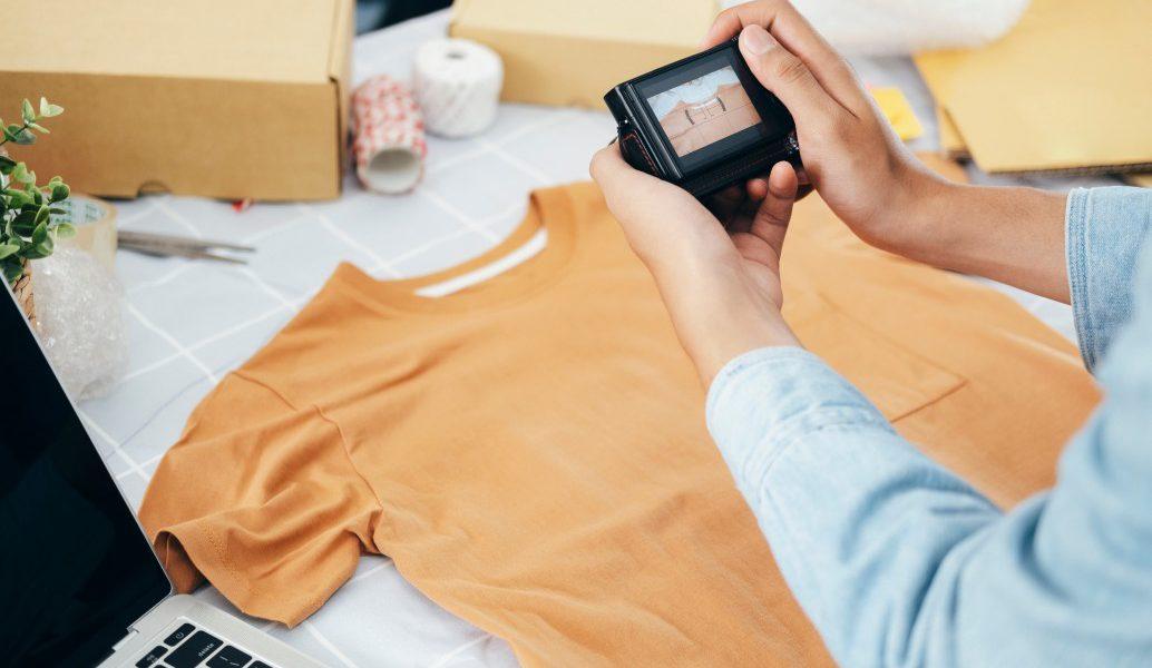 Imagem de uma camiseta amarela sobre uma mesa branca com pequenas caixas de encomenda ao redor e um notebook. Por cima da imagem, uma pessoa vestindo camisa azul fotografa a mesa com uma câmera.